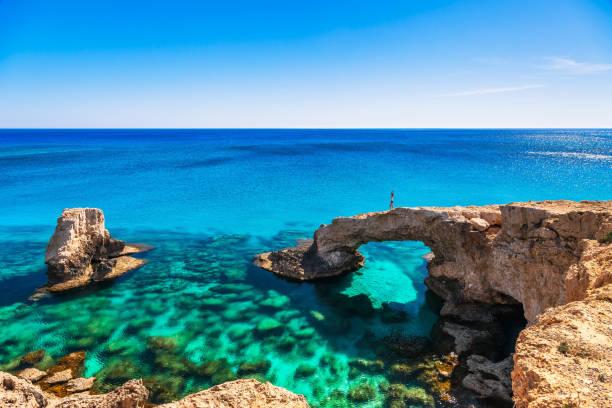 woman on the beautiful natural rock arch near of ayia napa, cavo greco and protaras on cyprus island, mediterranean sea. legendary bridge lovers. amazing blue green sea and sunny day. - cyprus стоковые фото и изображения