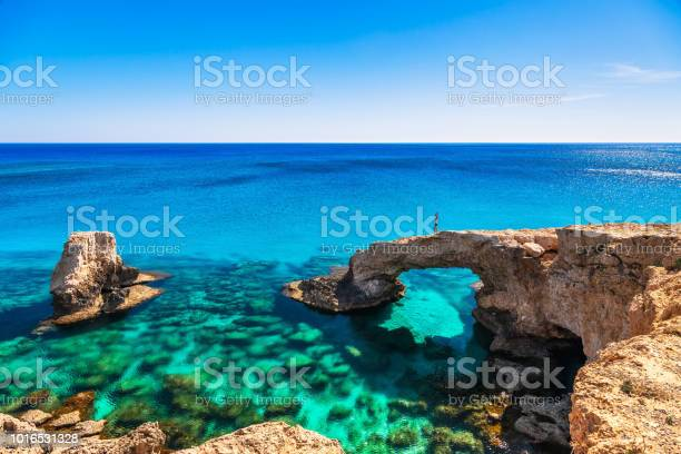 Photo of Woman on the beautiful natural rock arch near of Ayia Napa, Cavo Greco and Protaras on Cyprus island, Mediterranean Sea. Legendary bridge lovers. Amazing blue green sea and sunny day.