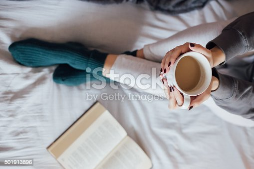 501914364istockphoto Woman on the bed with book and coffee 501913896