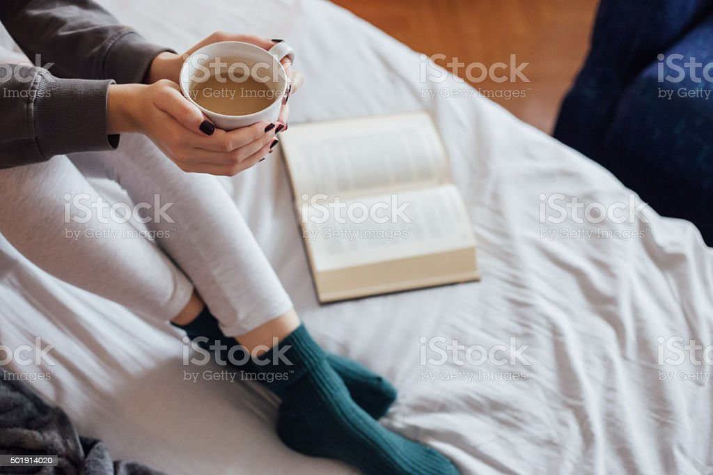 Woman on the bed with book and coffee stock photo