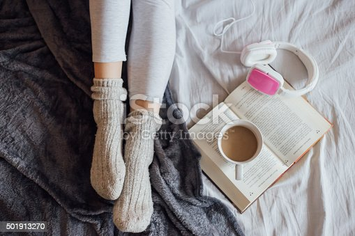 501914364istockphoto Woman on the bed with book, coffee and headphones 501913270
