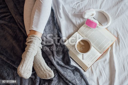 501914364istockphoto Woman on the bed with book, coffee and headphones 501913364