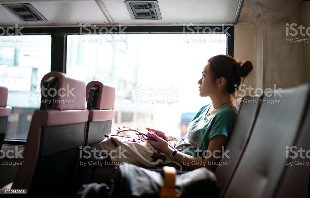 在香港公共汽車上的女人透過窗戶看 - 免版稅一個人圖庫照片