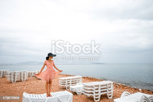 476618818 istock photo Woman on the deserted beach with many sunbeds 476619956