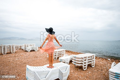 476618818 istock photo Woman on the deserted beach with many sunbeds 476619968