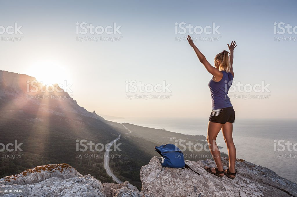Woman on the mountain at sunrise stock photo