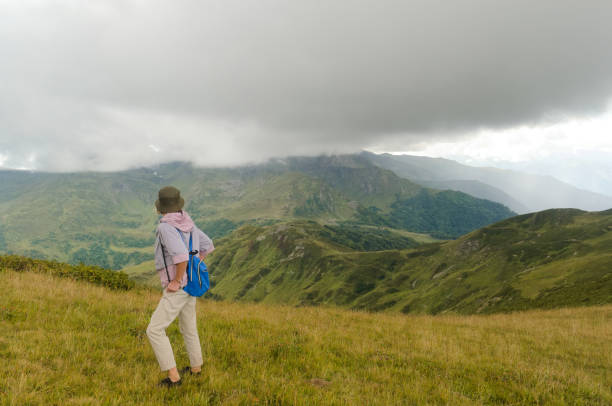 Woman on the mountain side under low clouds stock photo