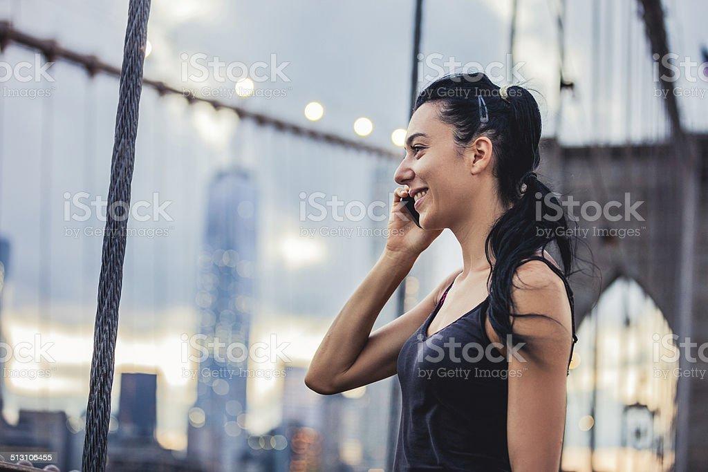 Woman on the phoen on the Brooklyn Bridge stock photo