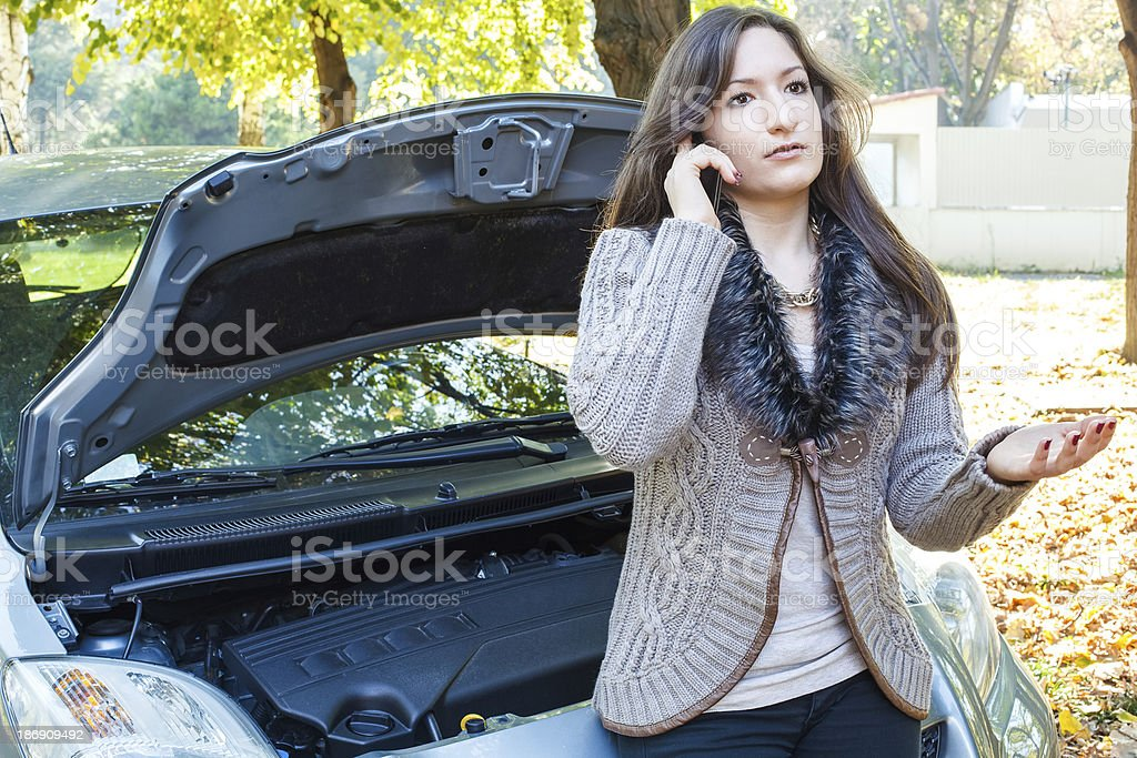 Woman on the phone asking for help beside her car royalty-free stock photo