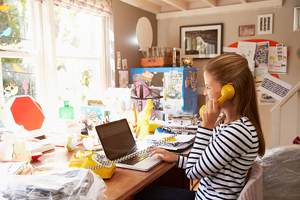 A woman on the phone at a cluttered desk at home Woman On Laptop Running Business From Home Office messy home office stock pictures, royalty-free photos & images