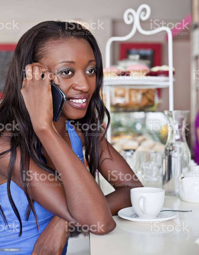 Woman on the phone Cheerful african woman sitting in cafe and talking on mobile phone. Adult Stock Photo