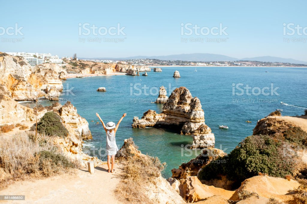 Woman on the rocky coastline in Lagos, Portugal stock photo