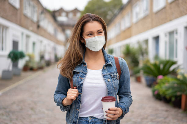 Woman on the street wearing a facemask and holding a coffee to go Portrait of a woman on the street wearing a facemask and holding a coffee to go - COVID-19 lifestyle concepts using mouth stock pictures, royalty-free photos & images
