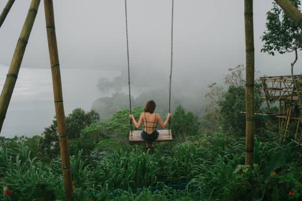 woman on the swing over the jungles and lake  in bali - balouço imagens e fotografias de stock