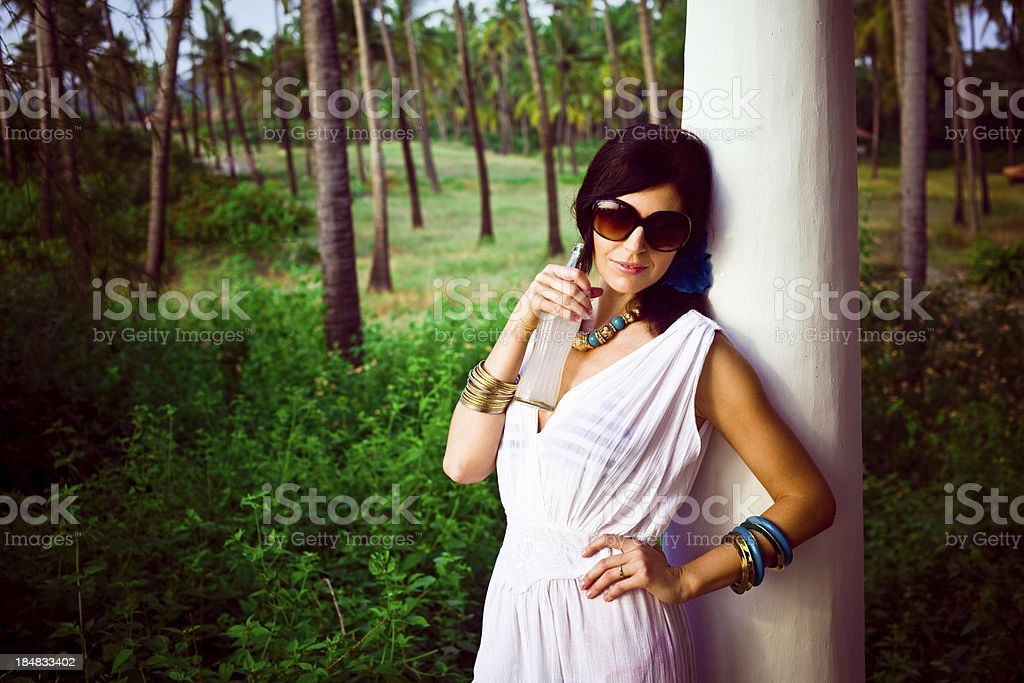 Woman on the tropical vacation Beautiful woman wearing sunglasses refreshing by cold drink with coconut palm grove in the background. 30-34 Years Stock Photo