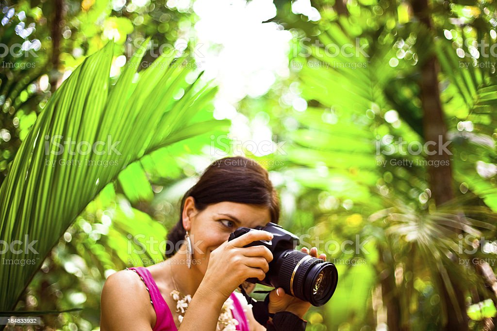 Woman on the tropical vacation Beautiful woman taking picture on the tropical vacation, palm grove in the background. 30-34 Years Stock Photo