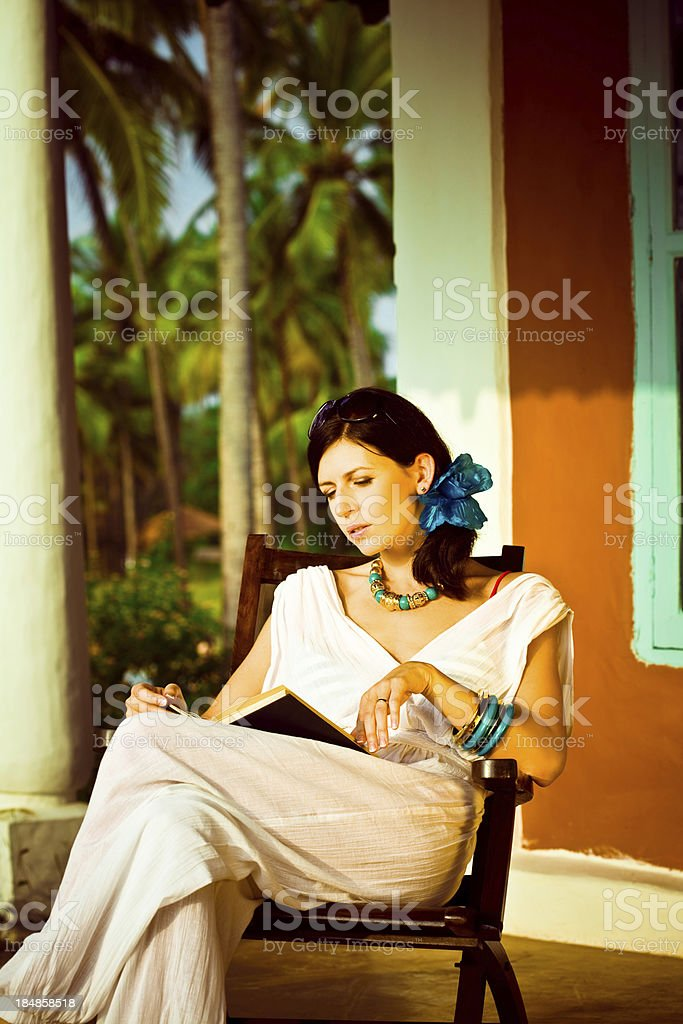 Woman on the tropical vacation Beautiful woman reading a book on the tropical vacation with coconut palm grove in the background. 30-34 Years Stock Photo