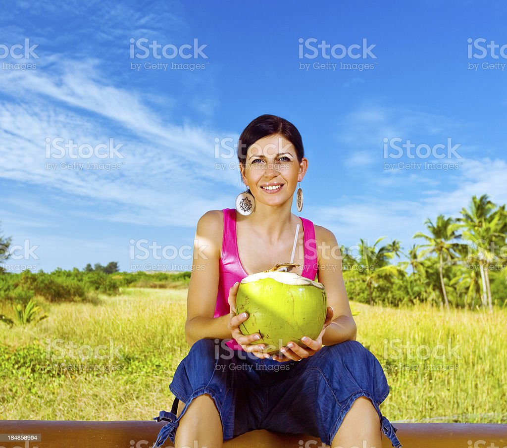Woman on the tropical vacation Pretty woman holding coconut water drink, smiling at camera. Coconut palm grove in the background. 30-34 Years Stock Photo