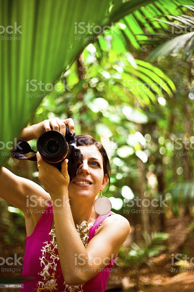 Woman on the tropical vacation Young woman taking picture on the tropical vacation, palm grove in the background. 30-34 Years Stock Photo
