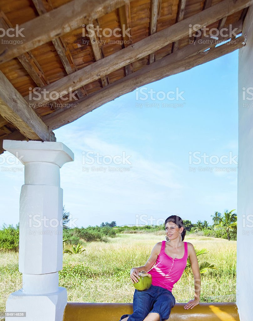 Woman on the tropical vacation Pretty woman sitting on rustic veranda and enjoying coconut water drink. 30-34 Years Stock Photo
