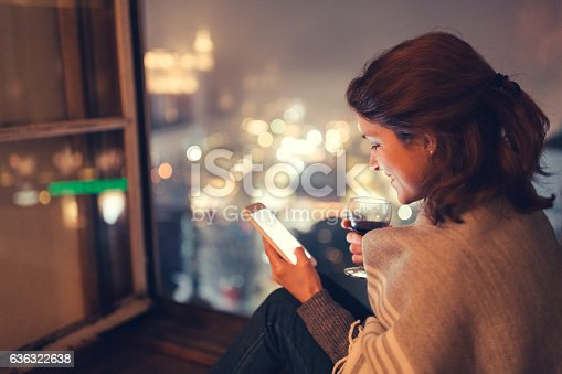 istock Woman on the window texting 636322638
