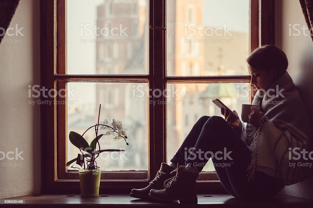 Woman on the window texting stock photo