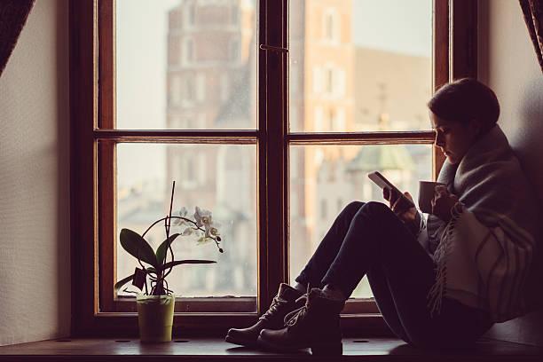 woman on the window texting - nostalgie telefon stock-fotos und bilder
