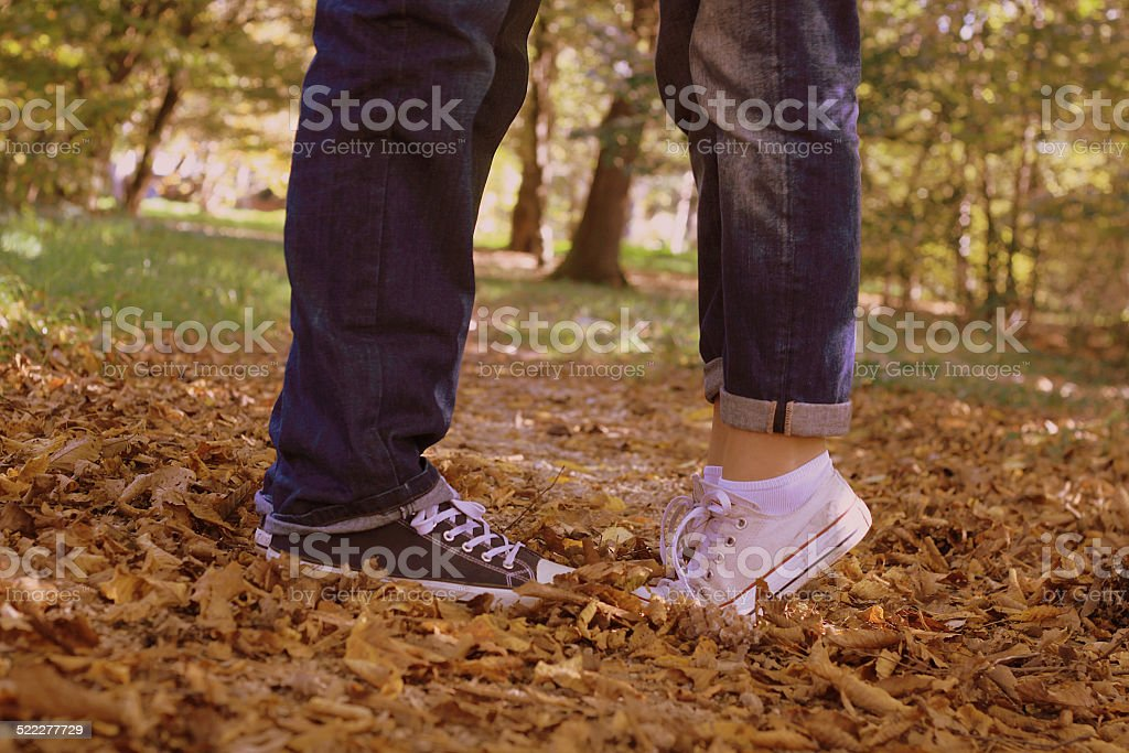 Woman on tip toes kissing man stock photo