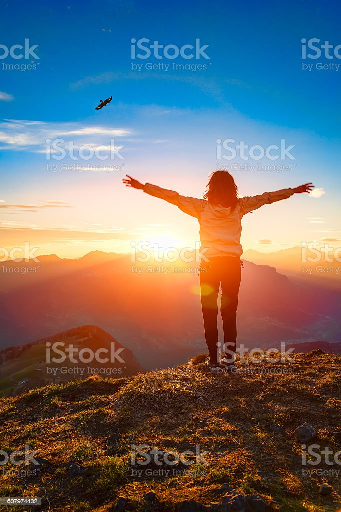 Woman on top of a mountain at sunset looks eagle stock photo