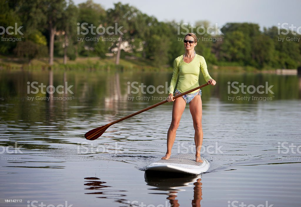 Woman on top of board paddling in the river stock photo