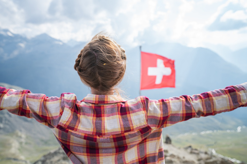 istock Woman on top of the mountain standing arms outstretched; Swiss flag in the Swiss Alps 1090247248