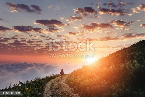 istock Woman on trail admiring the sunset with clouds and fog. 1158601083