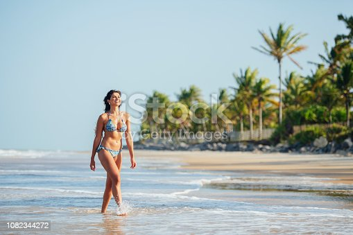 Woman walking along sea shore in swimwear, on vacation, palm trees in background