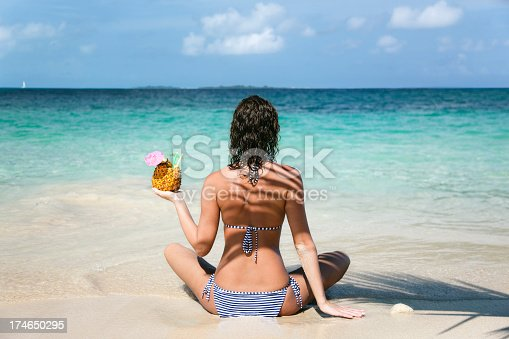 istock woman on tropical beach with a pineapple drink 174650295
