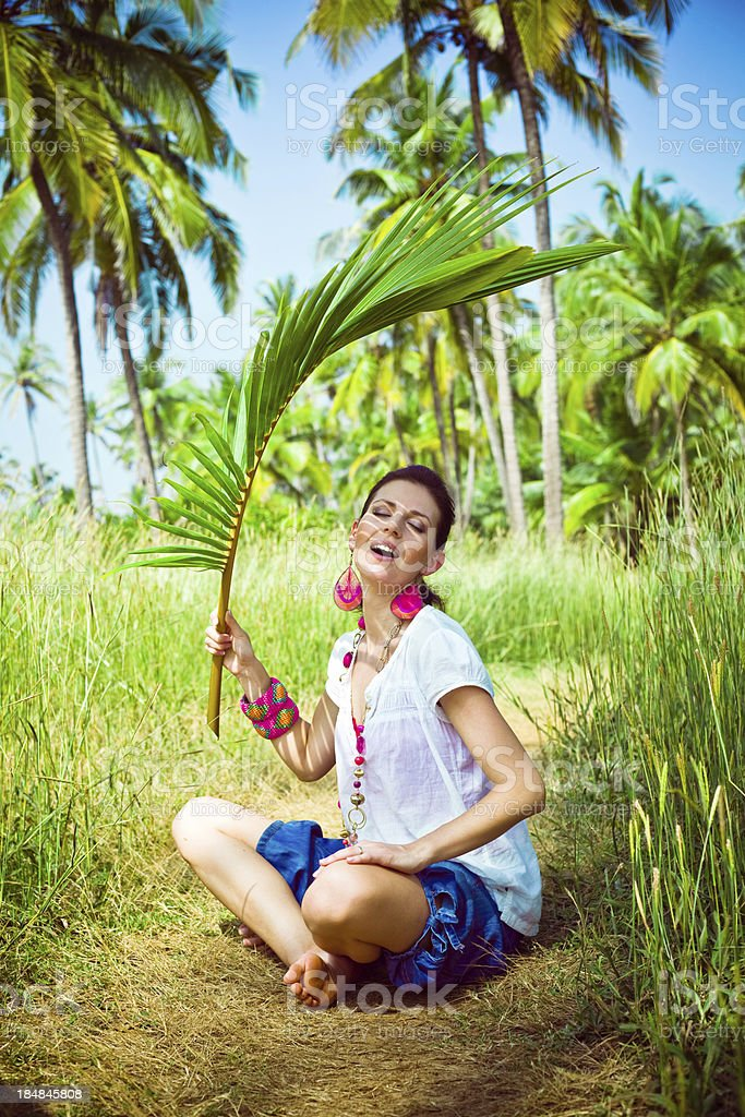Woman on tropical vacation Woman on tropical vacation, sitting on grass and holding palm leaf in her hand. Coconut palm trees in the background. 30-34 Years Stock Photo