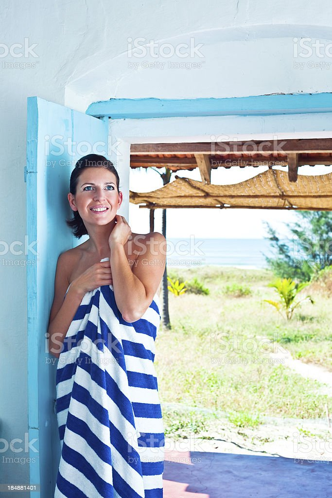 Woman on tropical vacation Smiling woman wearing stiped towel standing in the doorway with ocean landscape in the background. 25-29 Years Stock Photo
