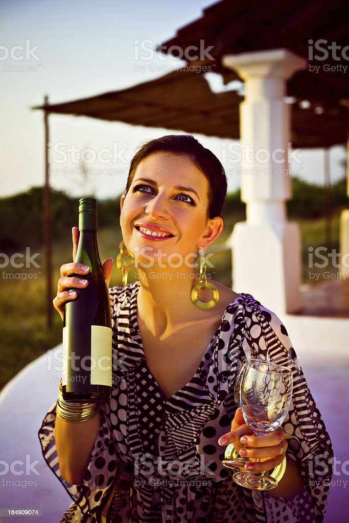 Woman on tropical vacation Beautiful woman holding wine bottle and glasses and enjoying her tropical vacation at sunset. 30-34 Years Stock Photo