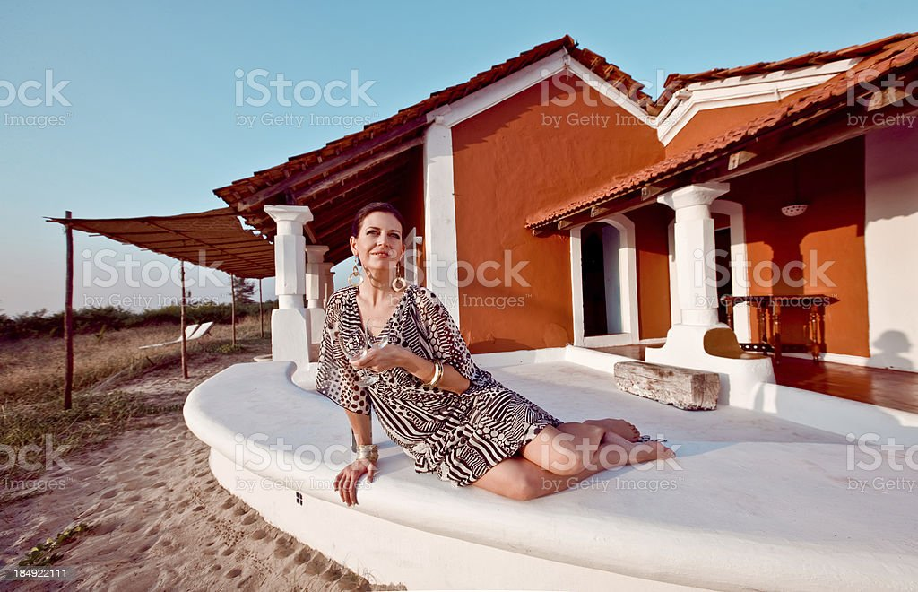 Woman on tropical vacation Beautiful woman wearing summer dress and gold jewelry holding wine glasses and enjoying her tropical vacation. 30-34 Years Stock Photo