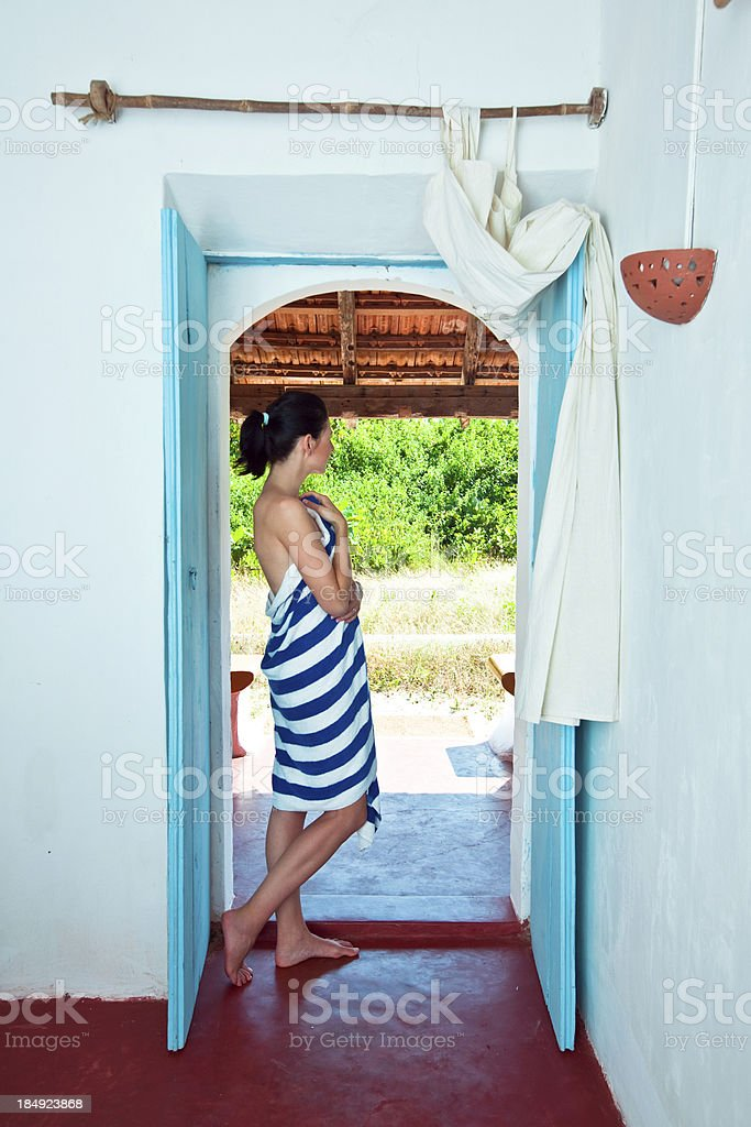 Woman on tropical vacation Woman wearing stiped towel standing in the doorway, looking in the distance. 25-29 Years Stock Photo