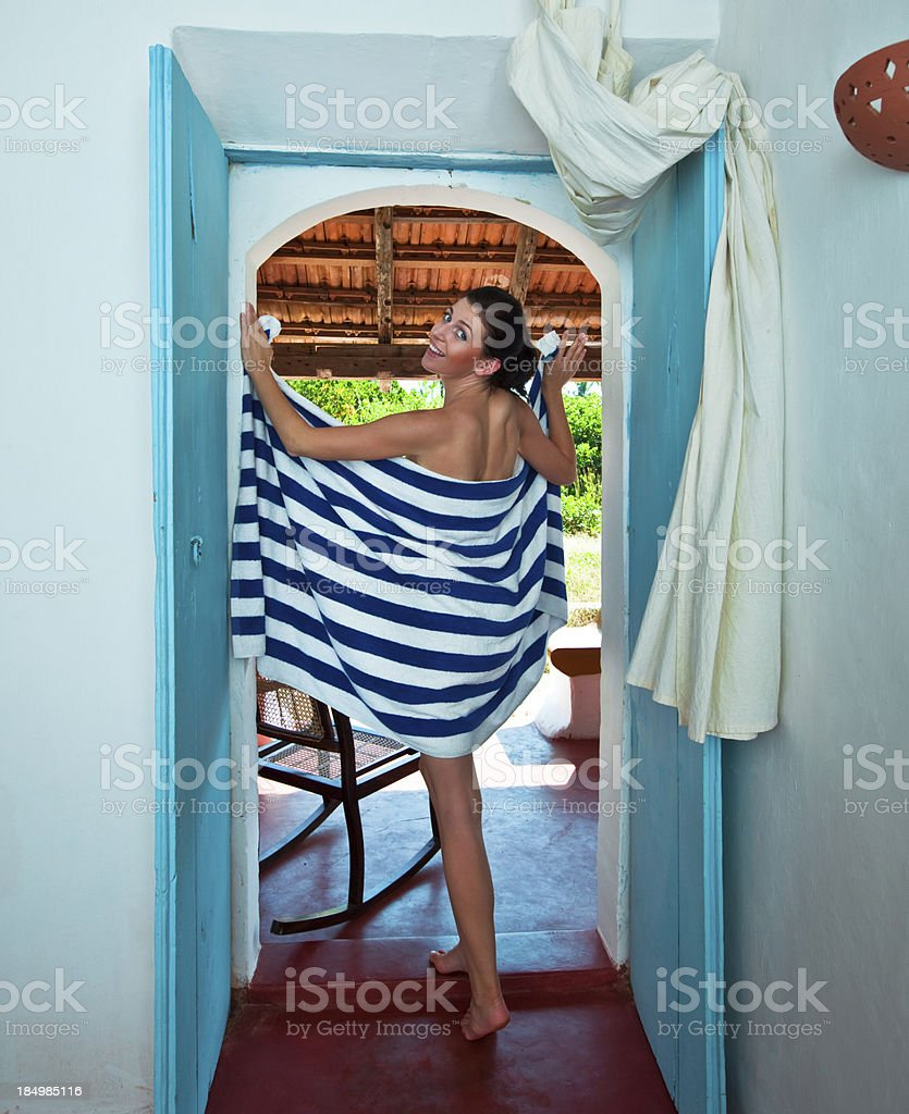 Woman on tropical vacation Woman wearing stiped towel standing in the doorway, smiling at camera. 25-29 Years Stock Photo