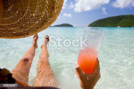 istock woman on vacation with tropical cocktail relaxing in Caribbean water 183039581