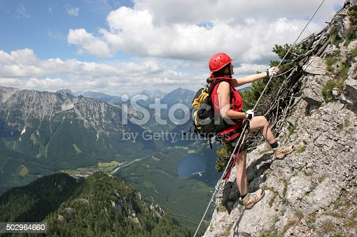 woman climbing on via ferrata to the peak of pfaffenstein. In the background lake named leopoldsteinersee near eisenerz in styria, austria