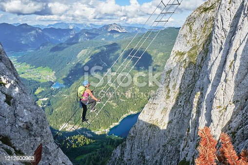 Woman on via ferrata ladder above Gosau lake, on the Intersport Klettersteig Donnerkogel route, in Austria. High angle view on a Summer day.