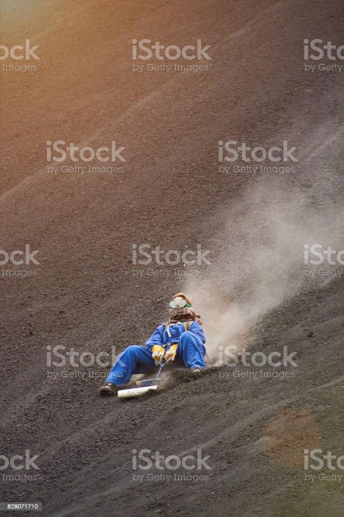 Woman on volcano sand boarding tour stock photo
