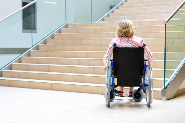 woman on wheelchair and stairs stock photo