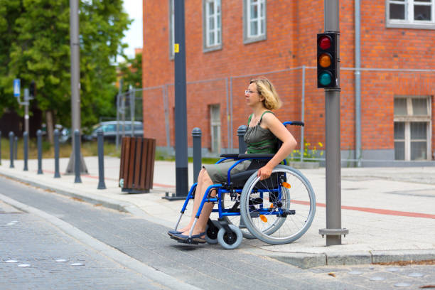 woman on wheelchair crossing the street stock photo