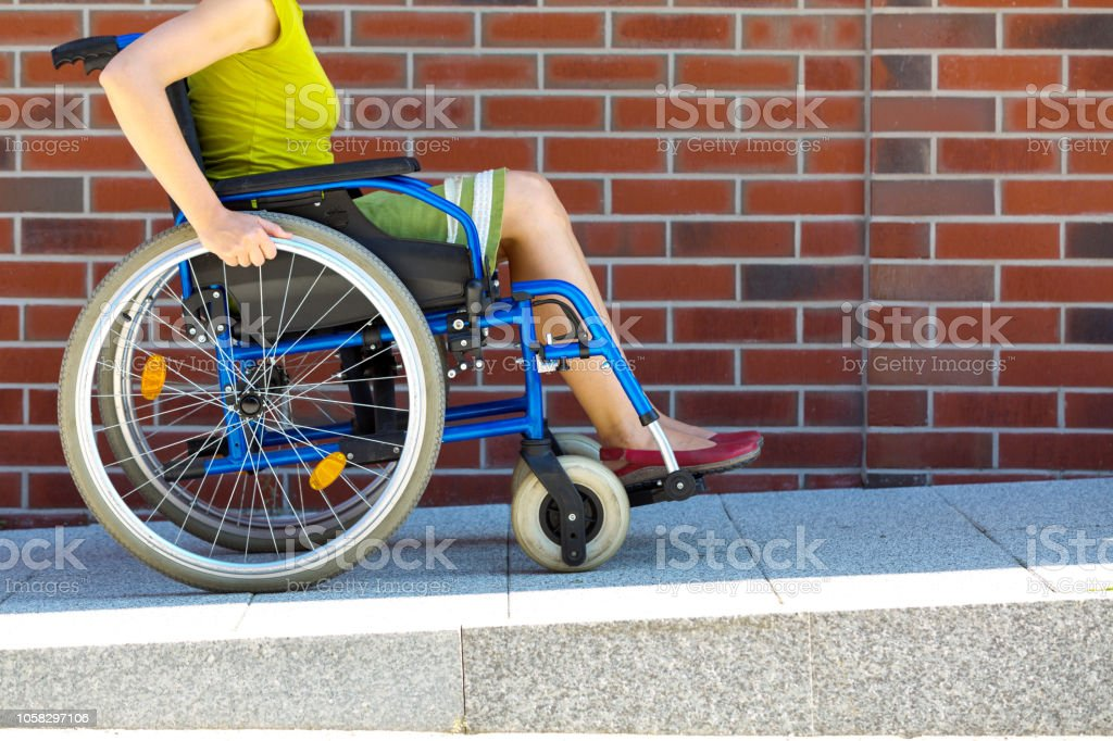 woman on wheelchair entering the platform adult woman on wheelchair entering the platform or driveway - side view Accessibility Stock Photo