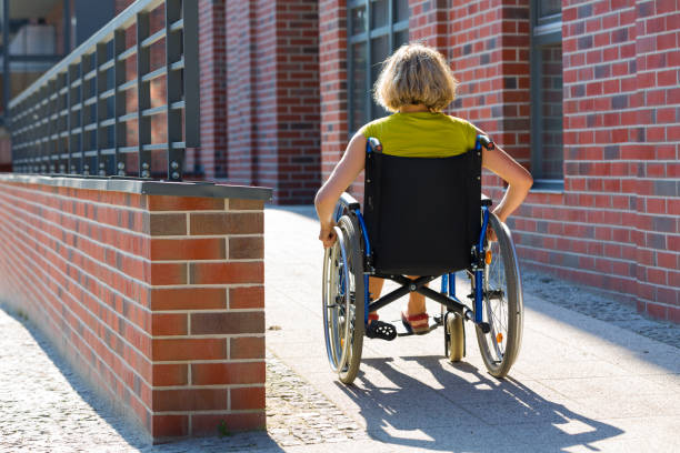 woman on wheelchair entering the platform stock photo