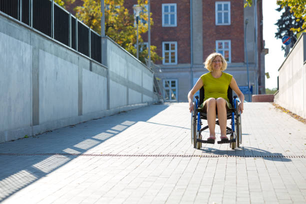 woman on wheelchair on the driveway stock photo