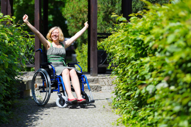 woman on wheelchair rising hands up stock photo